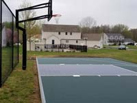 Green and black basketball court surface with hoop and basic rebounder in Agawam, MA.