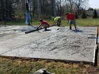 Creating a durable concrete base for a dark green and grey backyard basketball court in Agawam, MA.
