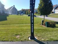 Driveway basketball hoop installation is the sort of thing you might find in Billerica, MA or a yard like yours. Featuring custom text on the post.
