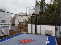 Small blue and grey basketball court with custom red H logo in Braintree, MA.