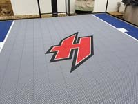 Closeup of custom red H logo on small blue and grey basketball court in Braintree, MA .
