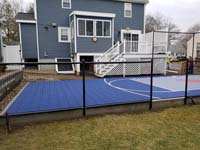 Blue and grey small backyard basketball court with custom red H logo in Braintree, MA, before finishing landscape and hardscape touches.