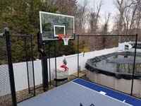 Corner detail of blue and grey basketball court in Braintree, MA, highlighting hoop and tall rebound fence.