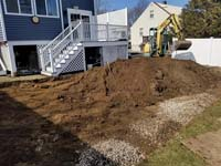 Excavation to prepare the site of a small blue and grey basketball court in Braintree, MA, adjacent to existing pool and featuring a custom H logo.