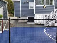 View through back fence of blue and grey basketball court in Braintree, MA, along with associated hardscapes.