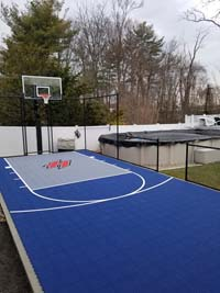 Small blue and grey backyard basketball court with custom H logo in Braintree, MA.
