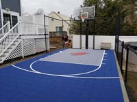 Small blue and grey basketball court in Braintree, MA, adjacent to existing pool and featuring a custom H logo.