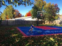 Backyard basketball court in Canton, MA. Whatever your sport, you could have a court surface and accessories of your own.