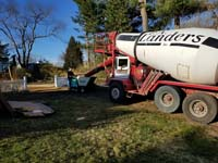 Cement mixer and small cart to transport batches to base form without truck needing to enter back yard during construction of dark green basketball court in Duxbury, MA.
