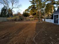 Prep work for construction of dark green basketball court in Duxbury, MA.