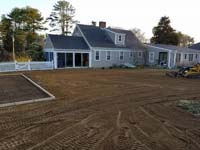 Backyard makeover context of base prep for installing dark green basketball court in Duxbury, MA.
