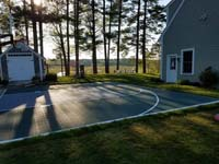 Backyard basketball court in Duxbury, MA. Surfaces for a variety of sports are available.