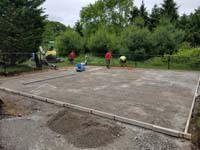 After excavation and removal of all organic material, it's packed gravel to go under the concrete base for a backyard court in Easton, MA.