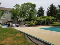 Off-white, tan, sand, beige, ecru? Whatever you call it, looks great with green on a home basketball court in Easton, MA, featuring view of existing pool in background.
