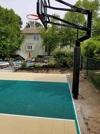 Sand and emerald green backyard basketball court in Easton, MA.