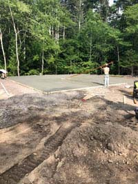 Similar view from finished picture to left, but bare ground in foreground and form with fresh cement being smoothed in to create a base for blue and gray residential basketball court in Easton, MA.