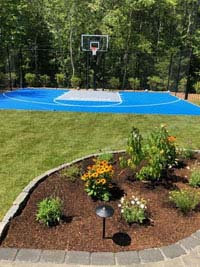 Blue and gray residential basketball court in Easton, MA. We partnered with Evergreen Landscaping of South Easton, whose work is highlighted in the foreground.