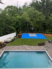 Blue and gray residential basketball court in Easton, MA, with pool in foreground.