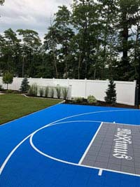 Side view of blue and gray residential basketball court in Easton, MA, highlighting landscaping by Evergreen beyond other side of court.