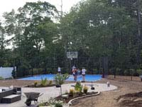 Kids shown on blue and gray residential basketball court in Easton, MA, with landscaping by Evergreen still in progress in foreground.