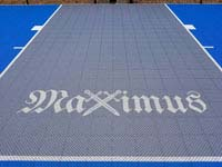 Blue and gray residential basketball court in Easton, MA, shown as closeup of custom Maximux logo with X as crossed swords..