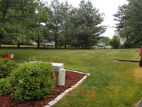 View of lawn where we installed a red and grey home basketball court in Groton, MA.