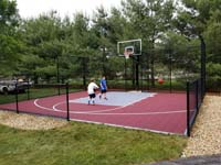 Kids using their new red and grey basketball court in Groton, MA.