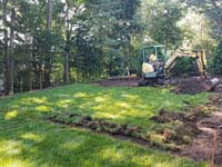 Removing lawn to make way for residential basketball court in shades of blue in Lexington, MA.
