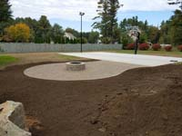 Under construction basketball court featuring Celtics logo, with fire pit, patio, and light for night play, in Londonderry, NH.
