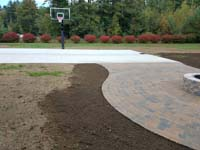 Detail work around a basketball court featuring Celtics logo, with fire pit, patio, and light for night play, in Londonderry, NH.