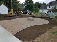 Detail work around partially complete basketball court featuring Celtics logo, with fire pit, patio, and light for night play, in Londonderry, NH.