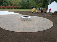 Partially completed construction of a basketball court featuring Celtics logo, with fire pit, patio, and light for night play, in Londonderry, NH.