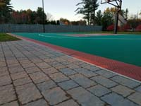 Closeup of periphery and surface of completed basketball court featuring Celtics logo, with fire pit, patio, and light for night play, in Londonderry, NH.