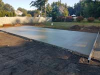 Drying con crete base for basketball court featuring Celtics logo, with fire pit, patio, and light for night play, in Londonderry, NH.