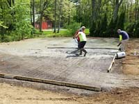 Pouring and leveling cement on compacted surface where a basketball court will be built.