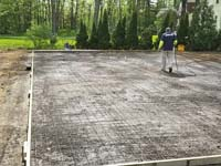 Form preparations for base construction for tan and green basketball court in Londonderry, NH.