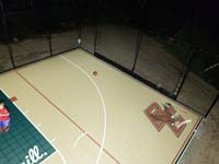 Right side of sand and green Londonderry court, with overhead lights on, highlighting custom BC Eagles logo.