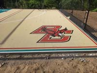 Closeup of custom Boston College Eagles logo on corner of sand and green backyard basketball multicourt in Londonderry, NH.