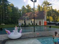 Green and black backyard basketball court adjacent to a pool in Marion, MA, following the finishing landscape touches.