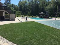 Green and black basketball court in Marion, MA, shown after completion of surrounding landscaping and pool.