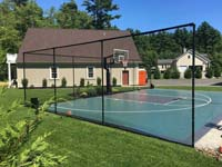 Beautiful green and black basketball court in finished landscape setting in Marion, MA.