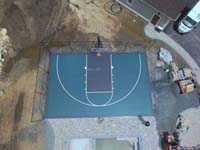 Green and black basketball court in Marion, MA, shown from above before landscape completion, courtesy of the owner's drone.