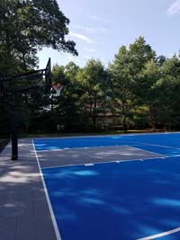 Large royal blue and titanium basketball court with golf seahorse logo at Bay Club in Mattapoisett, MA, shown from side looking at hoop at one end.