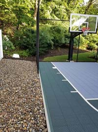 Context and portion of slate green and titanium small home basketball court in Needham, MA.