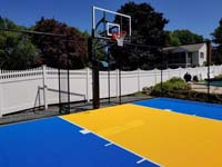 Royal blue and yellow residential basketball court in Stoneham, MA.