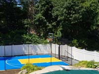 Royal blue and yellow basketball court and accessories in Stoneham, MA, viewed from adjacent covered pool.