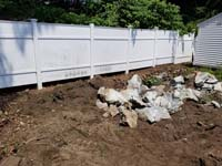 Rocks from broken boulder, awaiting removal to make way for royal blue and yellow basketball court and accessories in Stoneham, MA.