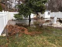 Flooding in poorly drained area of yard that will host a royal blue and yellow basketball court and accessories in Stoneham, MA.