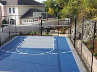 Backyard basketball court plus net for tennis, volleyball or pickleball, with landscaping, patio and wall in Stoneham, MA.
