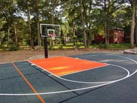 Graphite and orange residential basketball court replacing a dead pool in Walpole, MA.